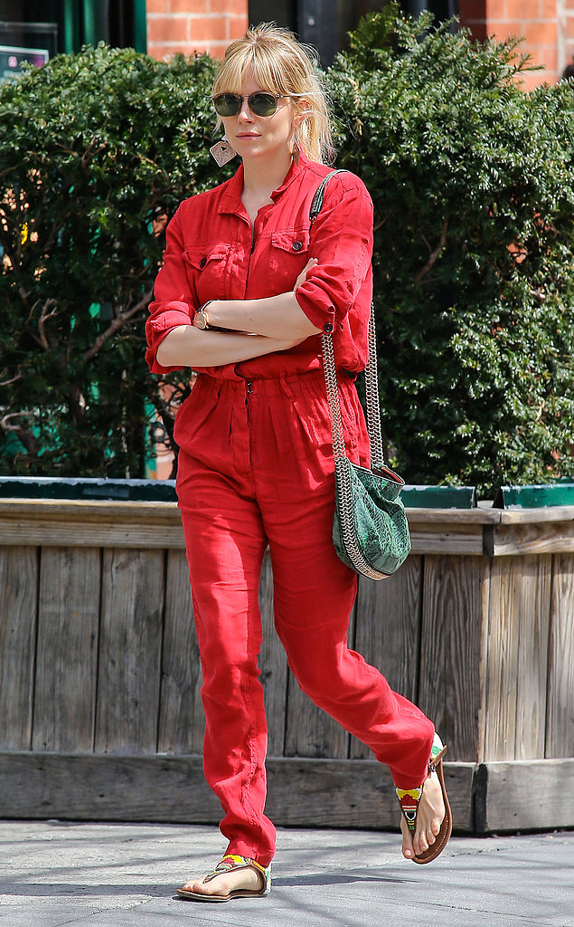 Sienna Miller stood out in a red jumpsuit, tribal sandals, and a green python-print Stella McCartney bag during a day out in NYC.