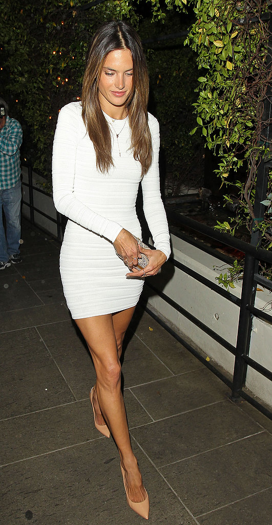 During a night out for her birthday, Alessandra Ambrosio put her long legs on display in a little white long-sleeved dress, then kept up the elongating effect via nude pointy pumps.