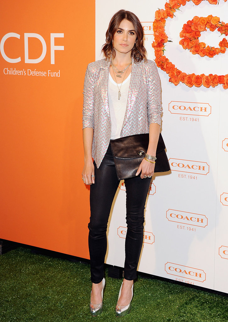 Nikki Reed dressed up a white t-shirt and coated jeans with a shimmery metallic blazer, silver pumps, and a black Coach Legacy Universal clutch.
