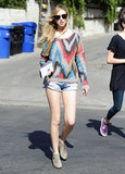 While out shopping in West Hollywood, Whitney Port matched a colorful printed sweater with denim cutoffs, round sunglasses, and zebra-print booties.