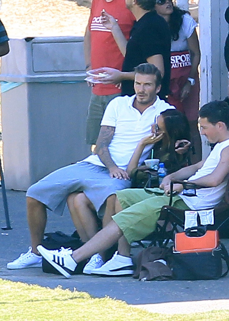 David snuggled up in Victoria's lap while they watched their boys play soccer in LA in September 2012.