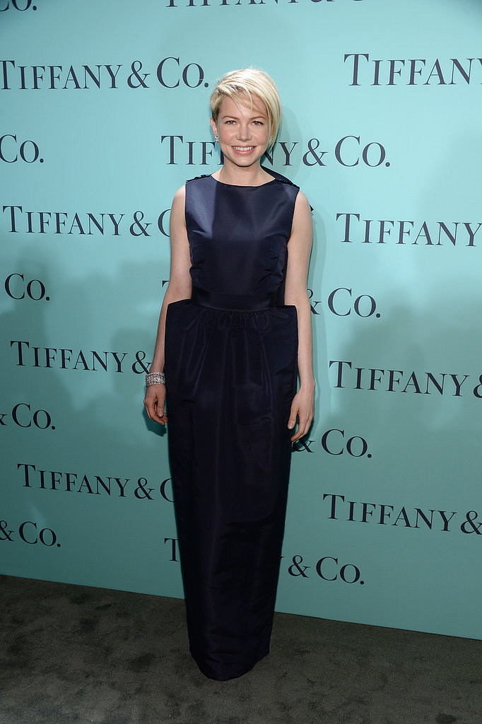 Michelle Williams looked chic in a navy gown by Katie Ermilio ($4,250) featuring a modern exaggerated hip detail.