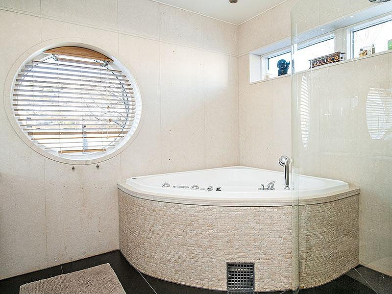 The corner bathtub is covered in beautiful white mosaic tile. Source: Sotheby's