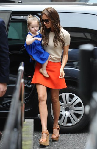 Victoria Beckham added a major jolt to her nude short-sleeved sweater and tan wedged sandals via a bright orange miniskirt in London.