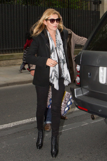 Kate Moss stepped out in London in all black, then spiced things up via a printed black and white scarf and a colorful Balenciaga bag.