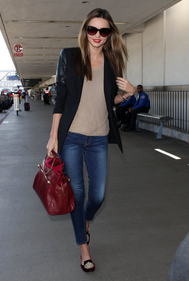 Miranda Kerr created a travel look with cropped Frame Denim and edgy touches via a leather-sleeved blazer, a rich red Viktor & Rolf bag, and velvet loafers.