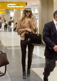 Rosie Huntington-Whiteley arrived at LAX airport in her signature cool style. She started with a tan crochet sweater and black leather pants, then added a soft gray fedora, aviator sunglasses, and a black suede satchel.