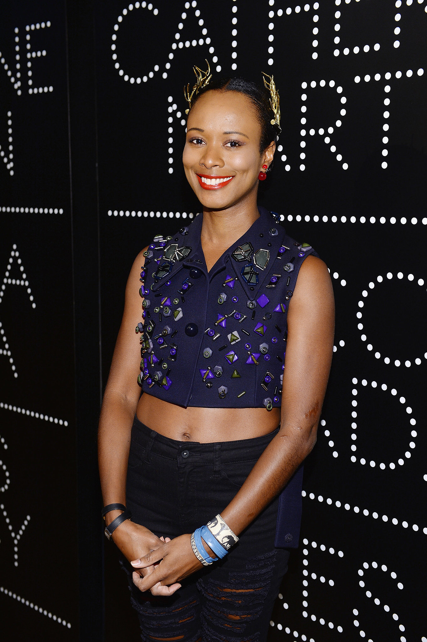 Shala Monroque showed off the season's belly-baring trend in an embellished sleeveless top paired with ripped jeans, a quirky gold headpiece, and stacked bracelets at the Prada and The Great Gatsby cocktail party.
