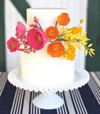 We adore the pop of color that the bright ranunculus bring to this otherwise simple cake.  Photo by Annie Edmonds via Green Wedding Shoes