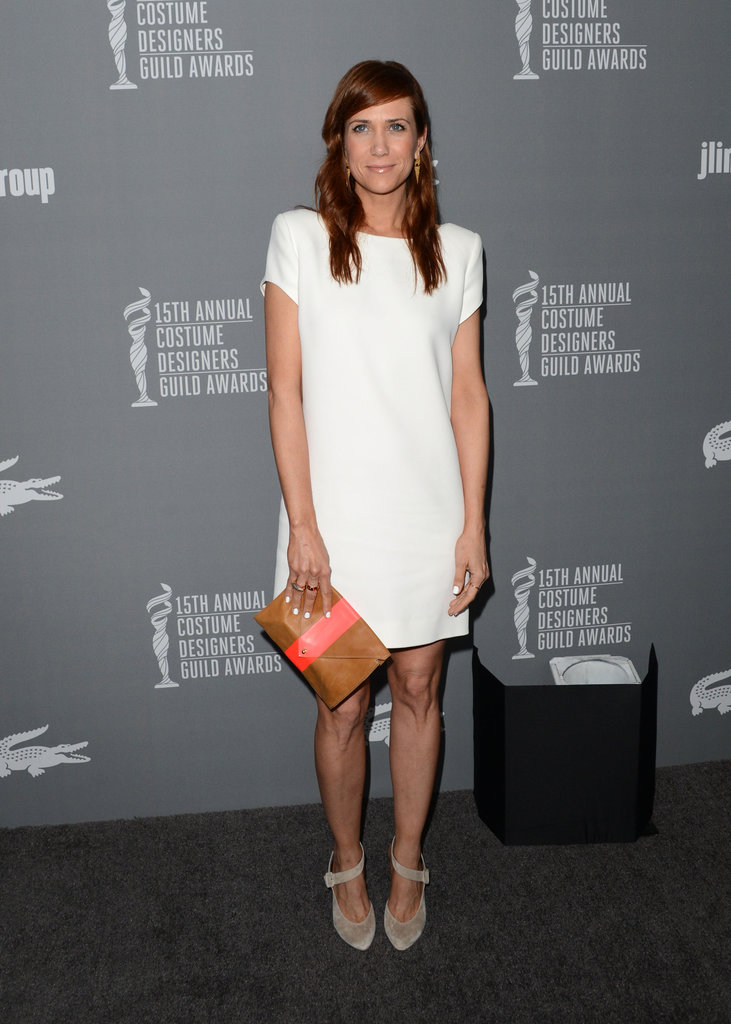 Kristen Wiig was playful in a white Saint Laurent t-shirt dress, gray suede pumps, and a two-tone envelope clutch at the Costume Designers Guild Awards in Beverly Hills.