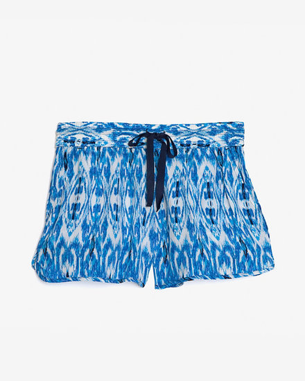 Upgrade your laid-back party look with a pair of festive printed shorts. We could see these Joie ikat-print silk shorts ($178) with a pair of metallic gladiators.