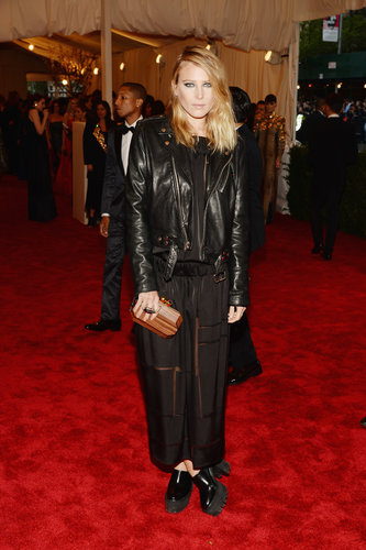 Dree Hemingway added a black leather biker jacket to her black sheer maxi dress, then added an au naturel touch via a wooden clutch.