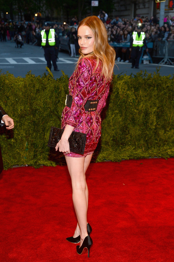 Kate Bosworth showed off her long legs in a bright pink beaded Balmain minidress, accessorized with a black studded belt, a beaded clutch, and black satin pumps.