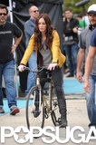 Megan Fox rode on a bike in a yellow jacket.