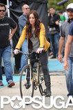 Megan Fox rode on a bike in a yellow jacket.