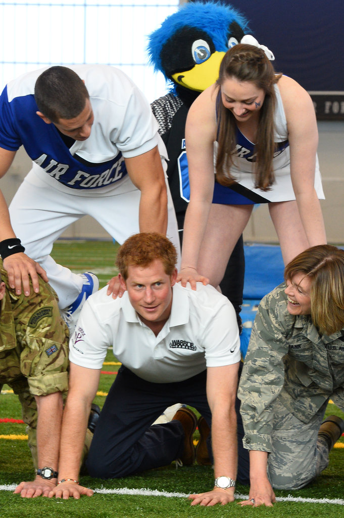 On Sunday, Prince Harry got wrangled into making a human pyramid with the US Air Force Academy's cheerleading team in Colorado Springs, CO.