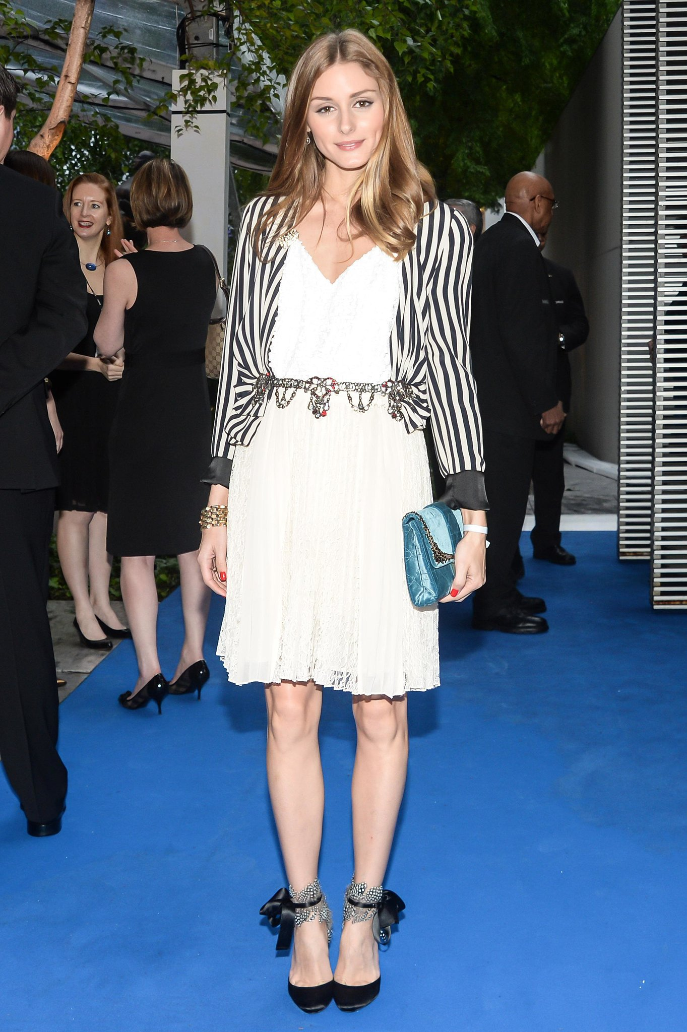 With a striped jacket, jeweled belt, and delicate ankle-strap heels, Olivia set her LWD apart from the rest of the cocktail party crowd at an event at the MoMA in May.