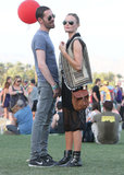Kate Bosworth added edge to her 2013 bohemian Coachella look — which included a black sheer overlay dress, tribal-print vest, and leather crossbody bag — with masculine buckle-detailed boots and unisex aviators.