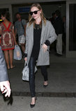 Kate layered up in an oversize tweed jacket, leather leggings, embroidered flats, and classic-cool shades after touching down at LAX in March 2013.