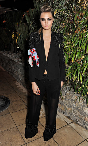 Cara Delevingne traded an evening gown for an embellished but laid-back tuxedo look at Calvin Klein's Cannes fete. She flashed her abs and furthered the sexy vibe with a smoky eye.