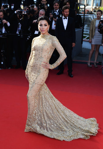 Eva Longoria showed off her curves in a dramatic long-sleeved gold lace and embellished Zuhair Murad gown at Le Passé. She finished off the look with Damiani earrings.