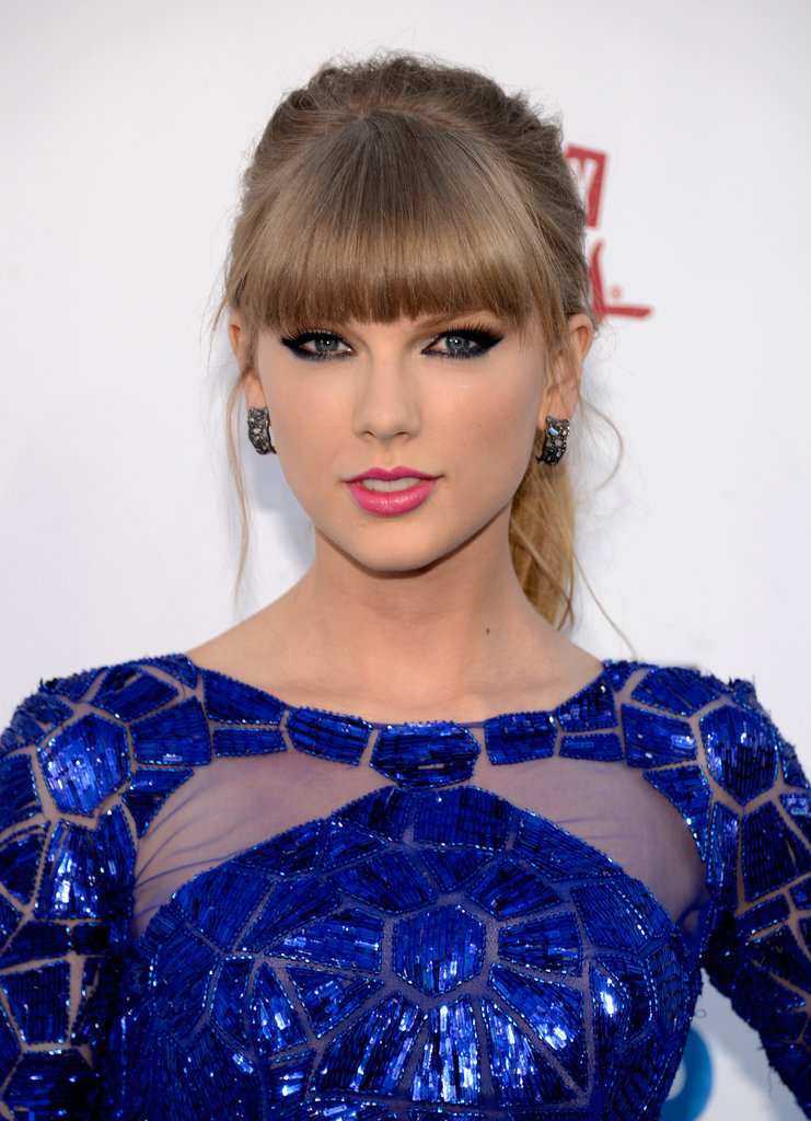 Taylor Swift stuck to what works best for her: thick black and blue liner, blunt fringe, and a bold pink lipstick shade.