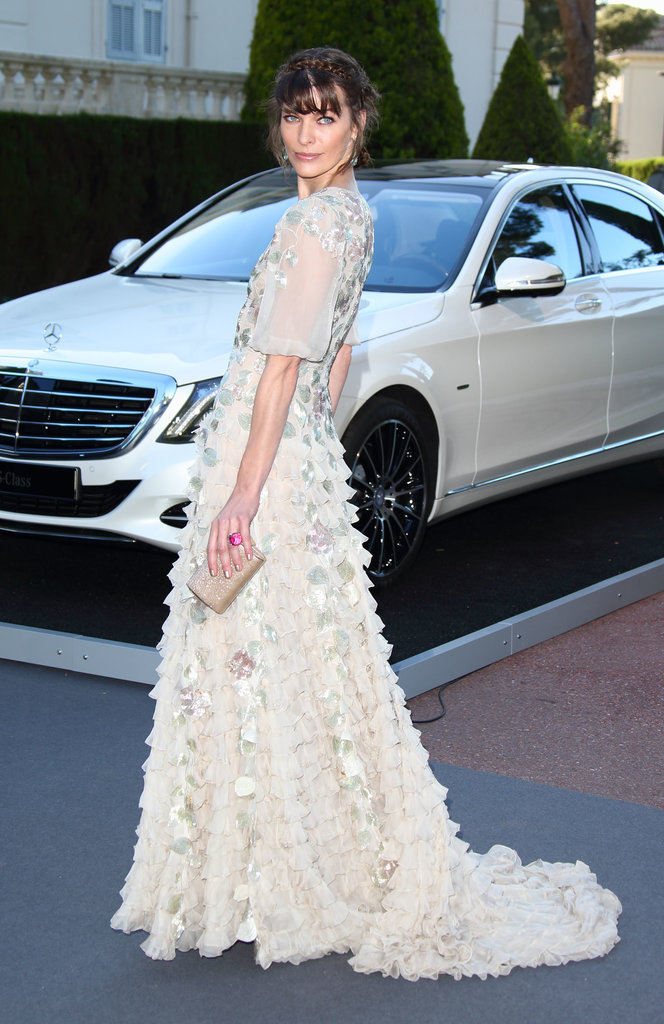 Milla Jovovich was happy to show off an ethereal ruffled floral gown upon her arrival.