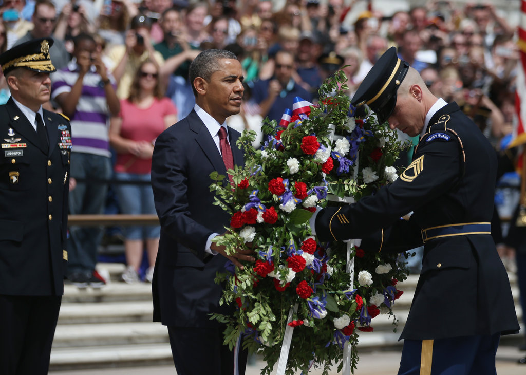 The president positioned a commemorative wreath during a ceremony at Arlington National Cemetery.