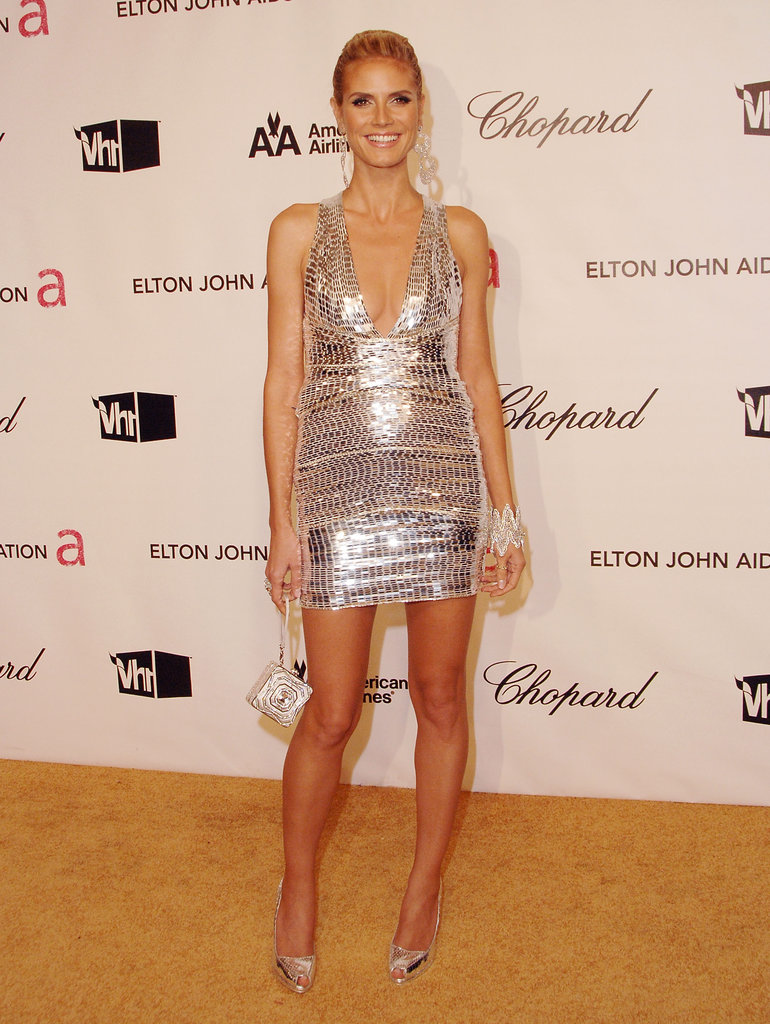 This list would be incomplete without the high-octane mirrored, metallic halter and coordinating pumps — not to mention her statement cuff, diamond drop earrings, and glittering minaudière — Heidi wore for Elton John's 2008 Oscars afterparty.