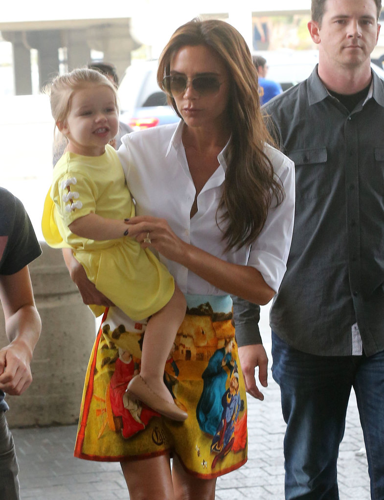 Harper Beckham gave her best smile while traveling through LAX with her mom, Victoria Beckham, in June.