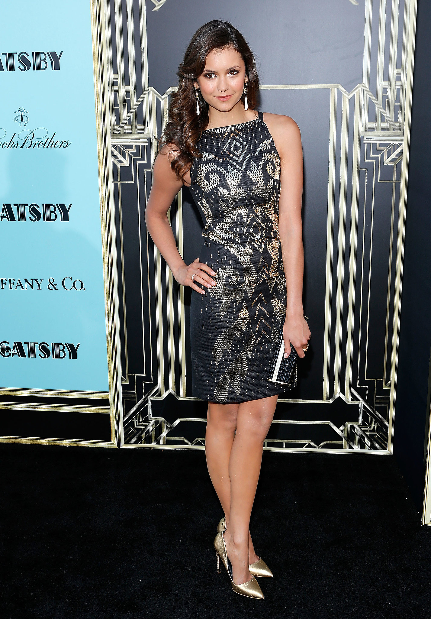 Glistening in an embellished Versace dress and metallic gold Rupert Sanderson pumps, it's clear Nina Dobrev is embracing her celebrity star power one dazzling creation at a time.