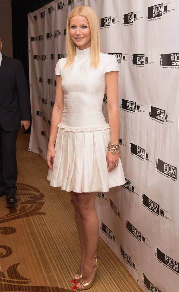 Gwyneth Paltrow paired a little white Alexander McQueen dress with gold peep-toe pumps and a chunky gold chain bracelet by Pomellato at a film gala in Chicago.