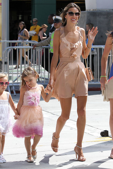 Alessandra Ambrosio waved in a peachy ruffled minidress and matching ankle-strap sandals in LA.