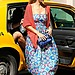 Jessica Alba exited an NYC cab looking bright as ever in a strapless printed Mara Hoffman dress, an orange cardigan, a blue Diane von Furstenberg crossbody bag, round Quay sunglasses, and Yosi Samra matching flip-flops.