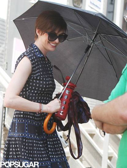 Anne Hathaway shielded herself from the NYC rain on Monday while filming scenes for Song One.