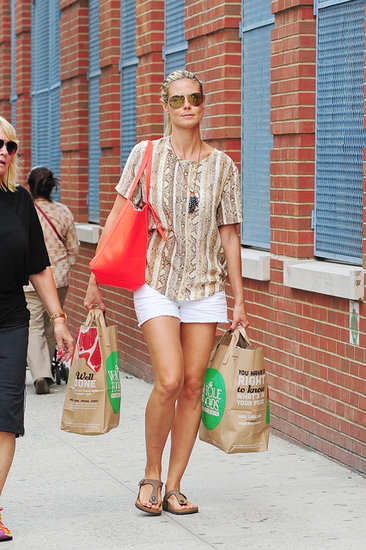 Heidi Klum jazzed up her white denim cutoffs with a snake-print tee, a bold red Vince Camuto tote bag, and mirrored aviators in NYC.