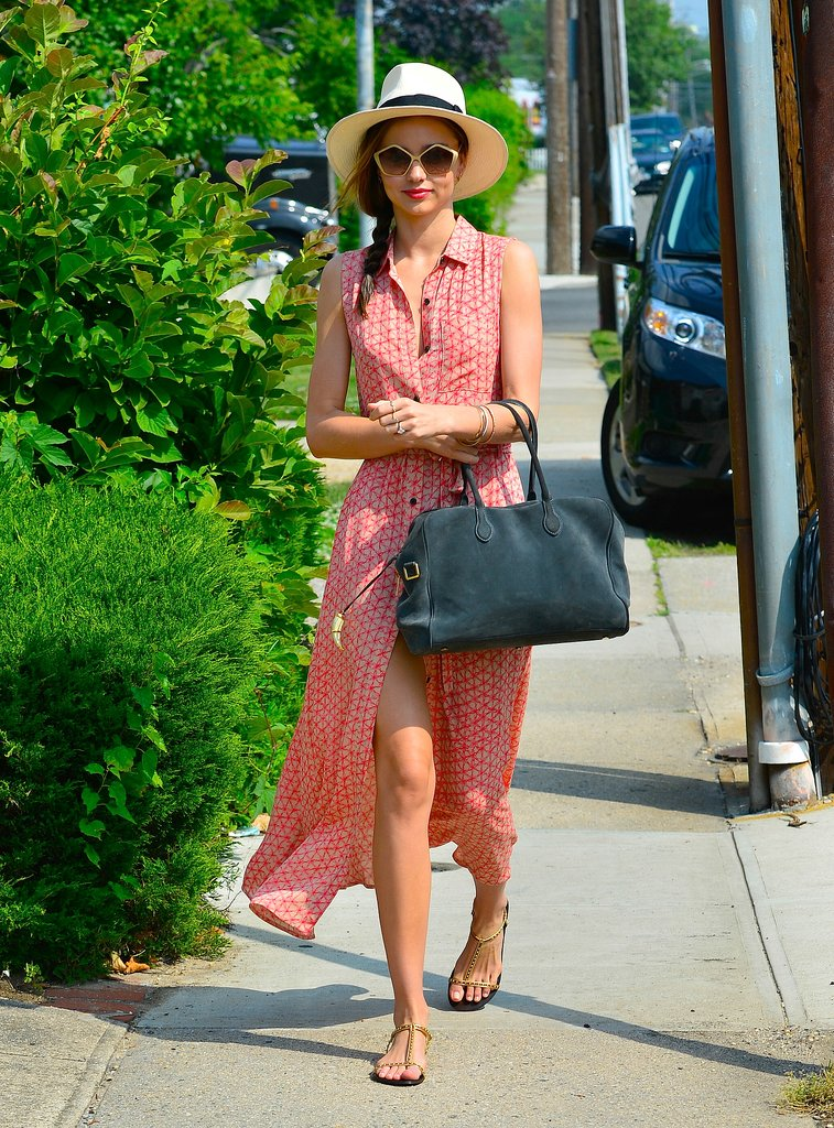 Miranda Kerr put her best Summer style forward in a printed maxi shirtdress, a Panama hat, gold Miu Miu sunglasses, and gold chain sandals in NYC.