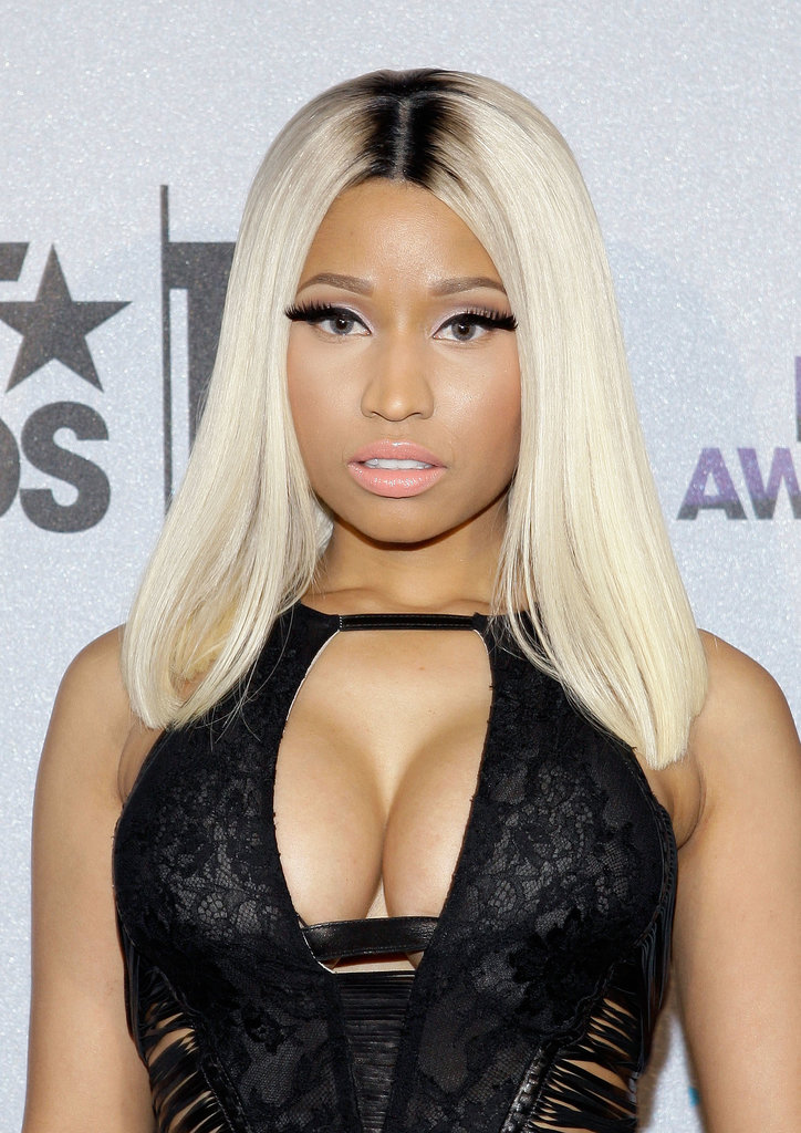 Nicki Minaj pared down her usually over-the-top makeup (read: rainbow highlights) for a more demure look: blond hair with dark roots, salmon lipstick, and thick false lashes.
