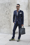 The staid navy suit feels personalized with a pocket square and trainers.