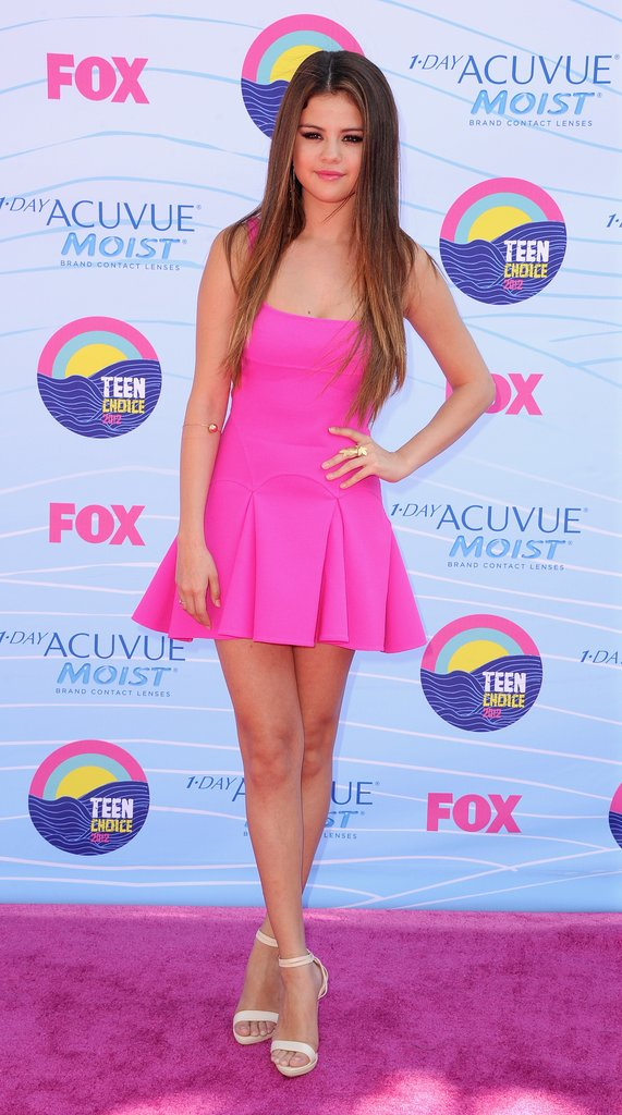 Selena Gomez let her hot-pink DSquared2 fit-and-flare take center stage — accessorizing with sleek strands, minimal makeup, and Hervé Léger stilettos — at the 2012 Teen Choice Awards.