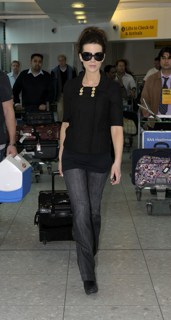 Kate traveled in a double-breasted knit short-sleeve cardigan, charcoal denim trousers, and fierce shades in 2008.