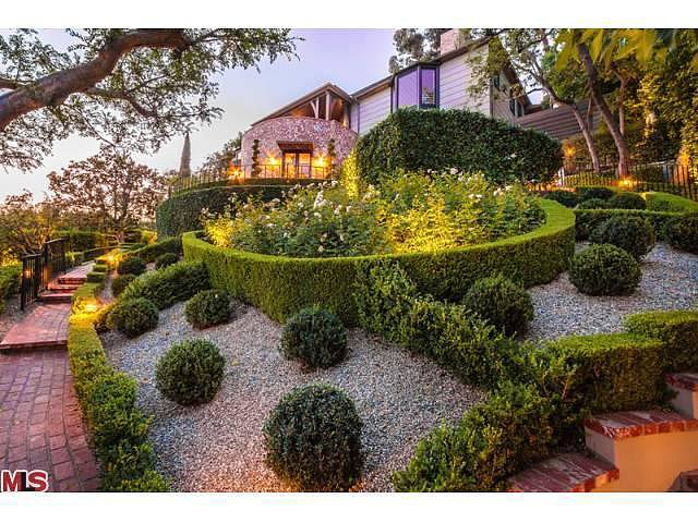 Beautifully primped landscaping adds an imperial garden feel to the front of the house.