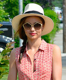 Miranda Kerr topped off her side braid with a hat and completed the chic look with geometric sunglasses and a bold lip.
