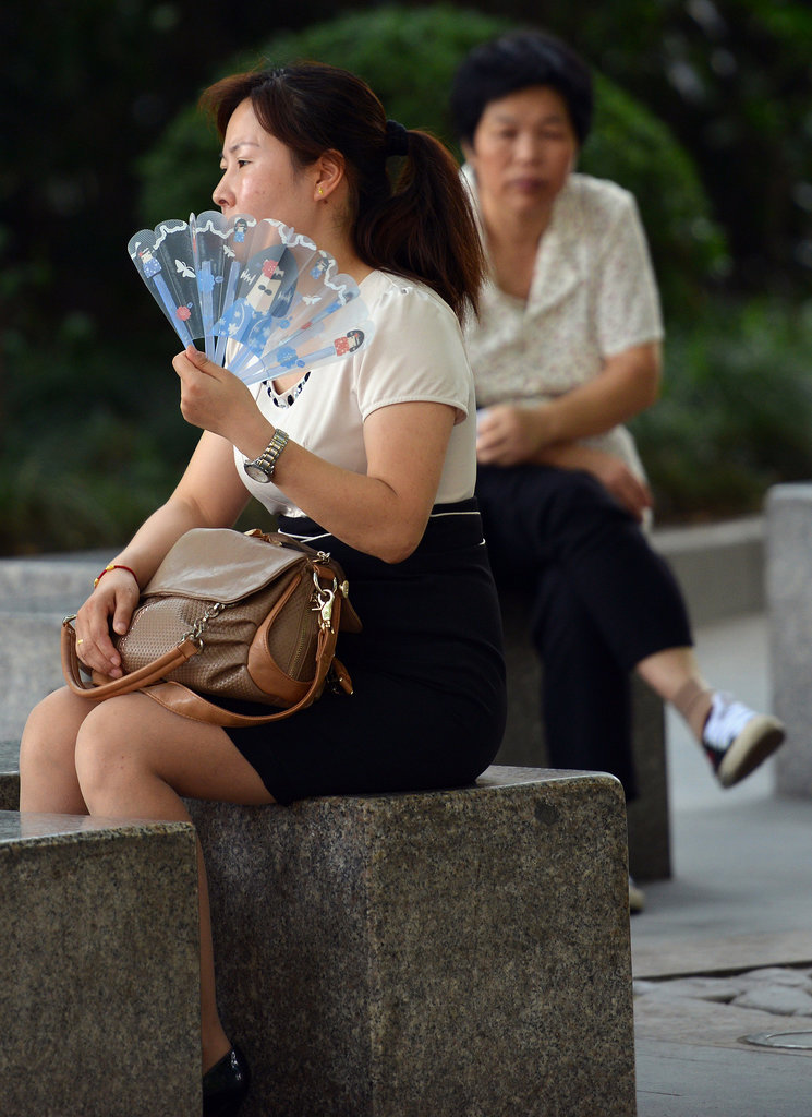 A woman fanned herself in Shanghai.