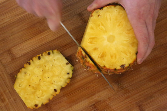 Run the knife down the length of the pineapple. You want to cut in deep enough so that all the prickly brown bits are cut off. I make about seven cuts, but you could do more or less, depending on how much you chop off, and how big your pineapple is.