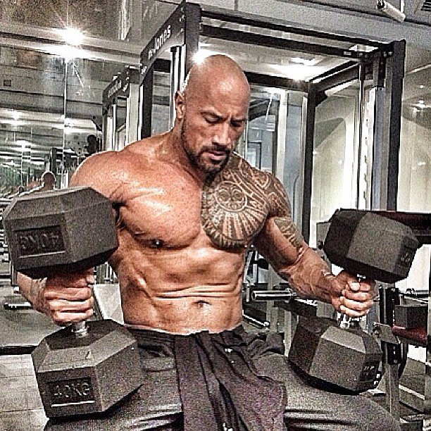 "Dwayne ""The Rock"" Johnson is apparently hitting the gym hard. He shared this picture while holding gigantic weights: ""Somethin bout the struggle so divine. This type of love is hard to define."" ~ Jay Z #NicklesAndDimes #BringIt"" Source: Instagram user therock"
