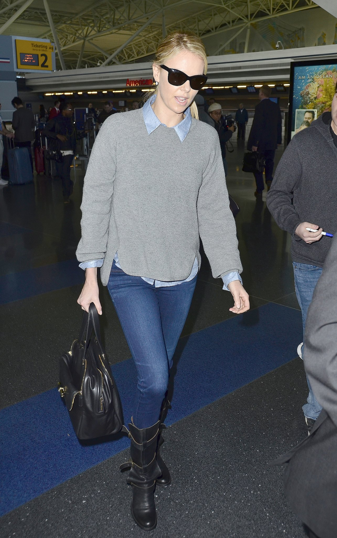 Airport couture never looked so good — Charlize toted a Jimmy Choo purse and flaunted her cool-girl Fiorentini + Baker boots while traveling.