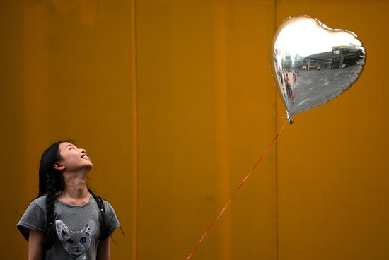 In Beijing, a woman smiled at her silver heart balloon.