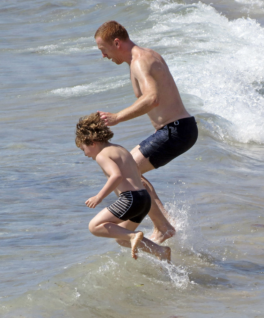 Damian Lewis and his son hopped in the waves.