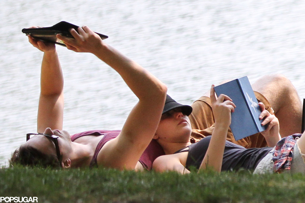 Jennifer Lawrence and Nicholas Hoult both read books on the grass.